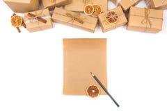 La lista di obiettivi vuota per natale e la carta kraft decorati presenta su un bianco Fotografie Stock