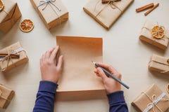 La lista di obiettivi vuota per natale in mani femminili e carta kraft decorate presenta Fotografie Stock