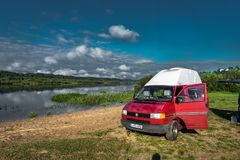 La LITHUANIE - août 2018 : Transporteur T4 de VW sur un petit lac en Lithuanie avec la vue vers le ciel bleu et quelques nuages E image stock