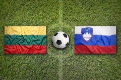 La Lithuanie contre Drapeaux de la Slovénie sur le terrain de football Photos libres de droits