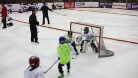 LA LITUANIA, VILNIUS - MAGGIO 2015: Passaggio del portiere il disco nel gioco fra le squadre di hockey dei bambini durante il cor video d archivio