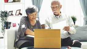 La livraison, courrier, expédition et concept de personnes - homme supérieur et boîte de colis d'ouverture de femme à la maison, clips vidéos