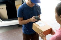la livraison d'homme de travailleur les boîtes à la maison de femme image libre de droits