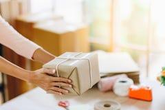 La livraison de mains de femme une boîte de colis images stock