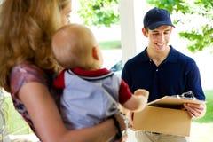 La livraison : Livreur vérifiant le nom sur la liste Photos libres de droits