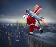 La livraison rapide des cadeaux de Noël Santa Claus prête à voler avec une fusée photographie stock libre de droits