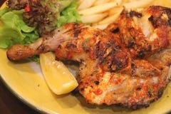 La llama asó a la parrilla el pollo picante con un pedazo de limón y de ensalada verde imagenes de archivo