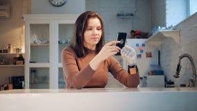 La llamada video está siendo hecha por una mujer joven con su brazo biónico Robótico real humano-como el brazo