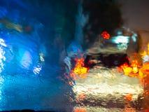 La lluvia borrosa cae en la ventanilla del coche con el bokeh de la luz del camino en fondo del extracto de la estación de lluvia foto de archivo libre de regalías