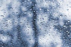 La lluvia cae el fondo del vidrio de ventanilla del coche Foto de archivo libre de regalías
