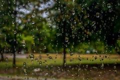 La lluvia cae en la ventanilla del coche con luz del sol, vidrio mojado, día lluvioso fotografía de archivo