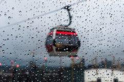 La lluvia cae sobre un vidrio mientras que un teleférico pasa cerca fotografía de archivo