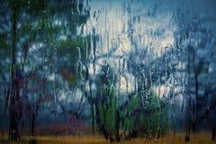 La lluvia corre abajo del cristal de ventana con los árboles Fotografía de archivo libre de regalías