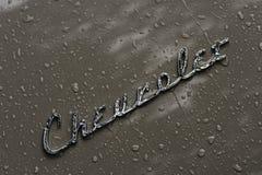La lluvia cubrió el coche y la insignia de Chevrolet Fotografía de archivo