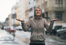 La lluvia de cogida de la mujer de la aptitud cae en la ciudad Foto de archivo libre de regalías