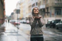 La lluvia de cogida de la mujer de la aptitud cae en la ciudad Imagenes de archivo