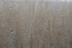 La lluvia del primer cae sobre el vidrio con el fondo natural fuera de la ventana imagen de archivo