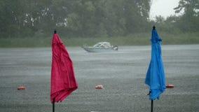 La lluvia del verano, tempestad de truenos, precipitación pesada en una playa vacía, los parasoles de playa solos se está colocan almacen de metraje de vídeo