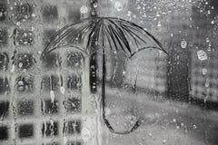 La lluvia, el paraguas se pinta sobre el vidrio imagen de archivo