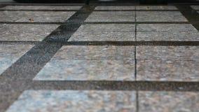 La lluvia está cayendo del cielo sobre el piso concreto en la ciudad y hace el piso mojado en la estación que llueve almacen de metraje de vídeo