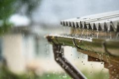 La lluvia fluye abajo de un tejado abajo Fotografía de archivo libre de regalías