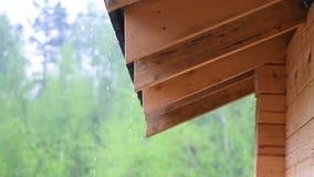 La lluvia fluye abajo del tejado de los descensos grandes de una casa de madera en tiempo lluvioso nublado metrajes