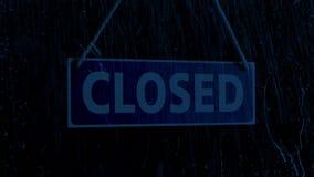 La lluvia golpea la ventana de tienda con la muestra cerrada en la noche metrajes