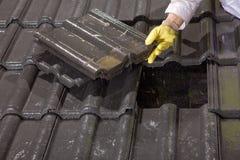 Trabajador en las tejas de tejado de la fijación del tejado Fotos de archivo libres de regalías