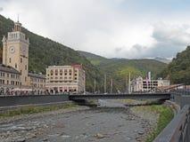 La località di soggiorno di montagna Rosa Khutor sull'argine del fiume, la torre di orologio, ponte, hotel Fotografie Stock Libere da Diritti