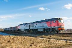 La locomotive et beaucoup de voitures de fret voyagent par chemin de fer, train de fret sur des rails dans la steppe photos stock