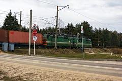 La locomotora de un tren de carga está cruzando el crossi ferroviario imagen de archivo