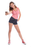 La longue adolescente à jambes heureuse a l'amusement avec la musique images libres de droits