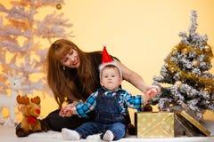 La longue femme de cheveux avec le bébé garçon près de l'arbre de Noël ouvre un cadeau Images stock