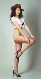 La longue fille de cheveux de brune ont l'amusement posant dans le studio dans l'étable de cowboy Photo stock