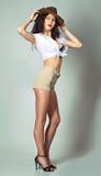 La longue fille de cheveux de brune ont l'amusement posant dans le studio dans l'étable de cowboy Image stock