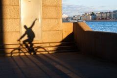 La longue ombre d'un cycliste Photo stock