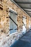 La longue vue de perspective d'un bâtiment en pierre avec l'écurie aiment des portes Photographie stock