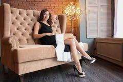 La longueur de la belle femme luxueuse s'asseyant sur un divan de vintage Photos stock