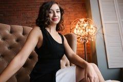 La longueur de la belle femme luxueuse s'asseyant sur un divan de vintage Photographie stock libre de droits