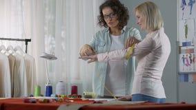 La longueur de mesure de styliste de la douille de client avec la bande, conseil au sujet de la couture vêtx banque de vidéos