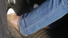 La longueur de mouvement lent des jambes femelles pressant le frein et l'accélération pédale à la voiture banque de vidéos