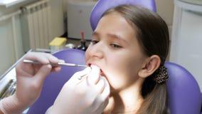 La longueur du plan rapproché 4k du dentiste dans des gants de latex inspectant le ` s de fille disent du bout des lèvres banque de vidéos