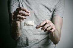 La lotta contro le droghe e l'argomento di tossicodipendenza: dedichi il pacchetto della tenuta di cocaina in una maglietta grigi immagine stock libera da diritti