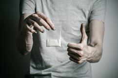 La lotta contro le droghe e l'argomento di tossicodipendenza: dedichi il pacchetto della tenuta di cocaina in una maglietta grigi fotografia stock libera da diritti