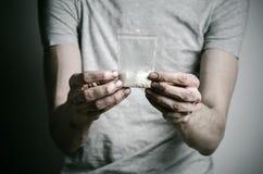 La lotta contro le droghe e l'argomento di tossicodipendenza: dedichi il pacchetto della tenuta di cocaina in una maglietta grigi immagini stock libere da diritti