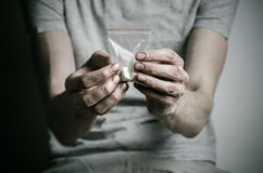 La lotta contro le droghe e l'argomento di tossicodipendenza: dedichi il pacchetto della tenuta di cocaina in una maglietta grigi fotografia stock