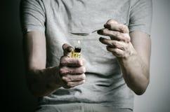 La lotta contro le droghe e l'argomento di tossicodipendenza: dedichi l'accendino del cucchiaio della tenuta e riscalda la droga  fotografia stock