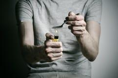 La lotta contro le droghe e l'argomento di tossicodipendenza: dedichi l'accendino del cucchiaio della tenuta e riscalda la droga  fotografie stock libere da diritti