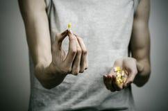 La lotta contro le droghe e l'argomento di tossicodipendenza: dedichi la tenuta delle pillole narcotiche su un fondo scuro immagine stock libera da diritti