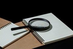 la loupe et le carnet sur le fond noir, étudient c Photo stock